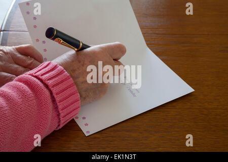 Close up femme âgée à l'aide de stylo pour écrire les salutations carte d'anniversaire Banque D'Images