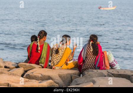 Habillés de couleurs vives, les filles locales famille sociable chat assis sur la plage rocheuse à la côte de Pondichéry, Banque D'Images