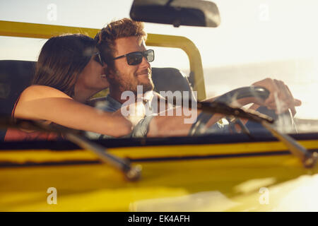 Jeune couple romantique partager un moment spécial pendant un voyage. Man driving car avec ma copine. Banque D'Images