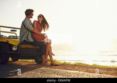 Jeune couple se regarder dans les yeux. Couple assis sur le capot de leur voiture profitant de l'instant, à l'extérieur. Banque D'Images