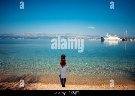 Woman looking at ferry sur la plage Banque D'Images