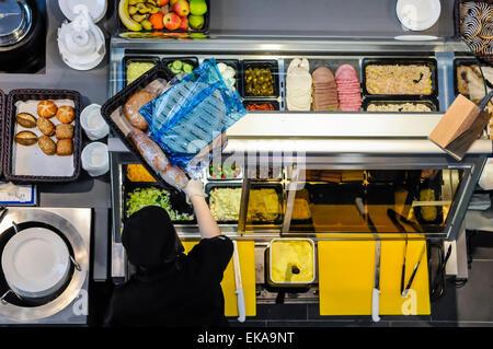 Une personne touche à un comptoir d'alimentation à un sandwich bar Banque D'Images