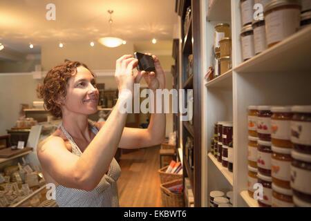Young woman photographing conserve sur smartphone dans l'épicerie bio Banque D'Images