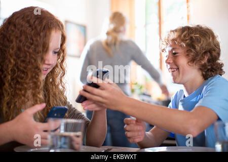 Frères et sœurs en utilisant smartphone à table à manger Banque D'Images