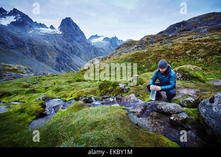 Male hiker eau de remplissage de bouteilles d'eau, Palmer, Alaska, USA Banque D'Images