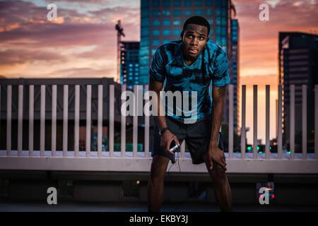 Young male runner en faisant une pause sur le toit de la ville au lever du soleil Banque D'Images