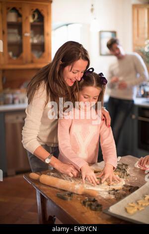 Mère et fille de formes de découpe dans la pâte pour faire des biscuits Banque D'Images