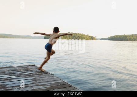 Garçon sautant dans le lac à partir de la jetée en bois, de l'Ontario, Canada Banque D'Images