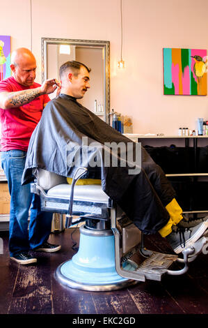 Jeune homme ayant sa coupe de cheveux Banque D'Images
