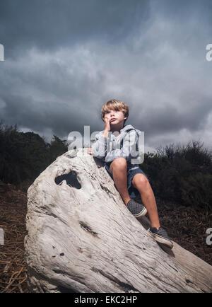 Jeune garçon assis sur la souche d'arbre contre le ciel d'orage