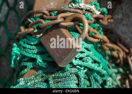 Un cadenas anciens sur un post avec chaîne et des filets de corde Banque D'Images