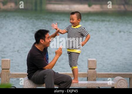 Père et fils, combat à l'épée qu'ils regardaient au Emperior's Palace Park, Kaifeng, province de Henan, Chine Banque D'Images