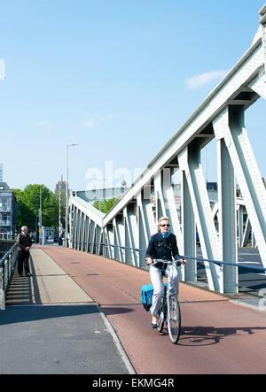 Vélo femme sur un pont sur un canal à Rotterdam, Pays-Bas. Banque D'Images
