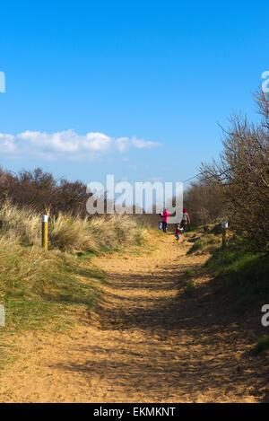 Les gens qui marchent vers le bas jusqu'à la plage à travers les dunes de la réserve naturelle locale Berrow, Somerset