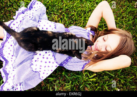 Girl lying on grass avec black chat calico Banque D'Images
