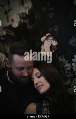 Un couple assis dans un bar éclairé bas, prendre un verre, se détendre. Banque D'Images