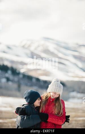 Un frère et une sœur serrant et rire ensemble à l'extérieur. Banque D'Images