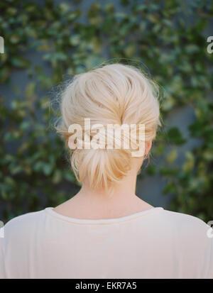 Une femme aux cheveux blonds disposés dans un noeud à la nuque. Banque D'Images