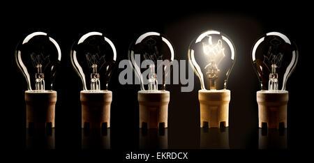 Dans la rangée d'ampoules avec un unique, shinning isolé sur fond noir Banque D'Images