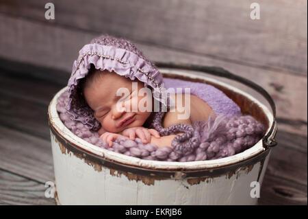 Mixed Race Woman Sleeping dans un seau en bois avec capot violet Banque D'Images