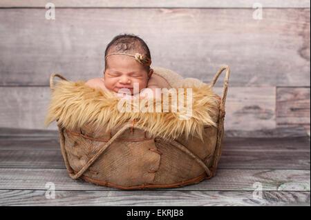 Smiling Naissance bebe Fille dormir dans un panier rustique. Banque D'Images