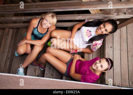 Trois jeunes amis féminins assis sur des marches de bois; California, USA Banque D'Images