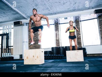 Groupe de l'homme et la femme sautant sur monter fort at gym Banque D'Images