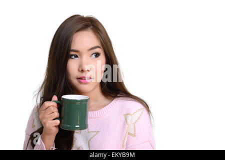 Pretty girl in pink sweater holding green coffee mug à la main sur fond blanc. Banque D'Images