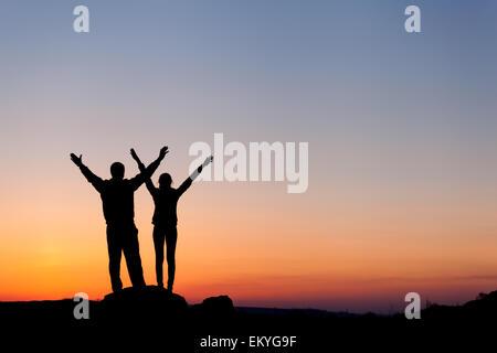 Silhouette de bonheur famille avec bras levés contre beau ciel coloré. Coucher du soleil d'été. Paysage Banque D'Images