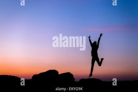 Silhouette of woman with arms raised up contre beau ciel coloré. Coucher du soleil d'été. Paysage Banque D'Images