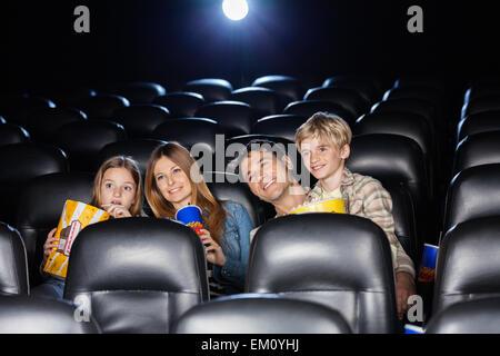 Smiling family regarder film en théâtre Banque D'Images