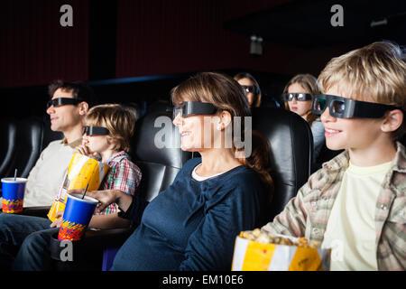 Les familles souriant le visionnage en 3D movie Banque D'Images
