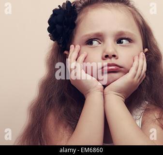 Jolie fille à la moue triste avec les lèvres et les mains sous la face. Closeup portrait bel enfant aux cheveux Banque D'Images