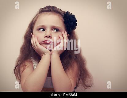 Belle fille à la triste avec la moue des lèvres. Closeup portrait of cute kid avec les cheveux longs. VIntage Banque D'Images