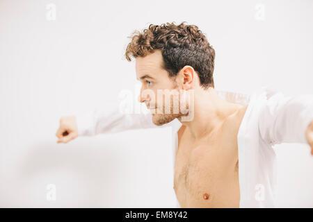 Young businessman putting on shirt dans l'appartement Banque D'Images