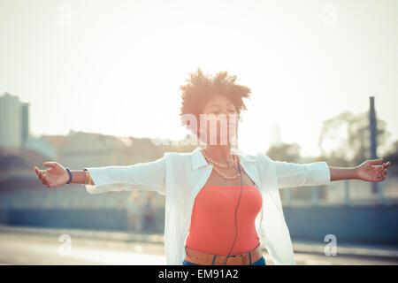 Jeune femme danse avec les bras ouverts vers le smartphone musique en ville Banque D'Images