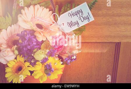 Heureux peut jour cadeau traditionnel de fleurs de printemps en cône orange accrochée à la poignée de porte sur la porte en bois, avec appliqués retro vint