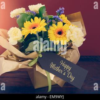 Heureux Jour mères cadeau de fleurs de printemps sur la table en bois sombre et rustique, l'arrière-plan rouge foncé style vintage retro appliquée avec fil