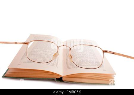 Verres sur un vieux livre vert isolated on white Banque D'Images
