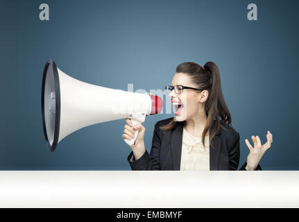 Young pretty businesswoman yelling sur megaphone