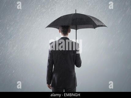 Young businessman standing in smart la forte pluie Banque D'Images
