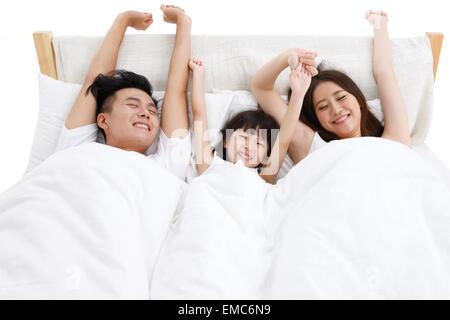 Le bonheur d'une famille de trois personnes dans le lit de la chambre à coucher s'est réveillé Banque D'Images