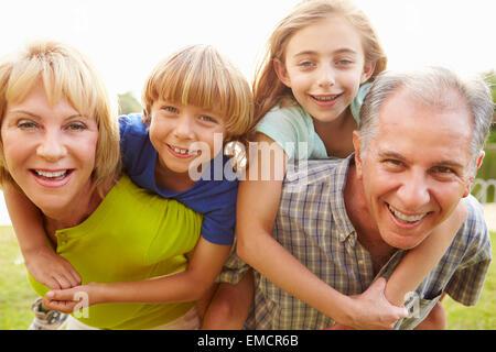 Les grands-parents petits-enfants donnant Piggyback Ride in Garden Banque D'Images