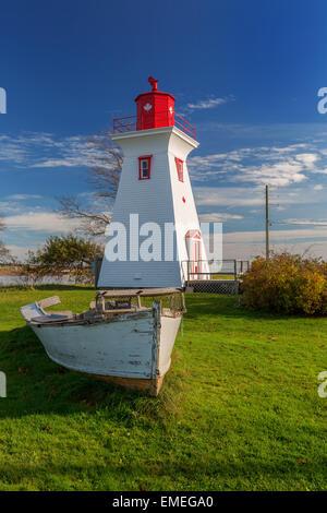 Phare et barque en bois avec un casier à homard perché sur c'est Bow à Victoria par la mer, l'Île du Prince Édouard, Banque D'Images