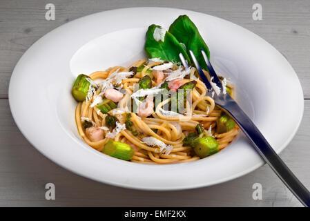 Des pâtes de blé entier aux asperges vertes, crevettes, l'ail sauvage (buckrams) pesto, copeaux de parmesan et feuilles Banque D'Images
