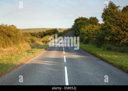 Route qui traverse la campagne de Pembrokeshire au coucher du soleil Banque D'Images