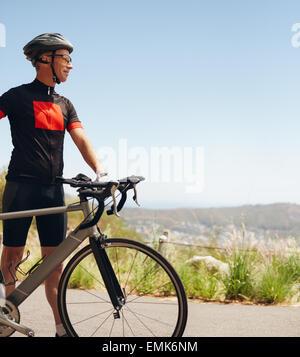 Image homme cycliste avec son vélo sur le côté du pays. Debout jeune cycliste avec son vélo à la voiture, à l'extérieur. Banque D'Images