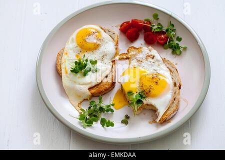 Le petit-déjeuner, des oeufs sur toasts avec le cresson et tomates cerises Banque D'Images