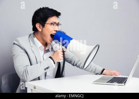 Businessman assis à la table et de crier dans un mégaphone sur ordinateur portable