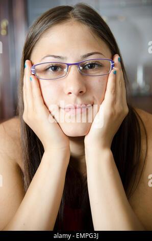 Jeune fille avec des lunettes et les mains sur une des joues. Banque D'Images